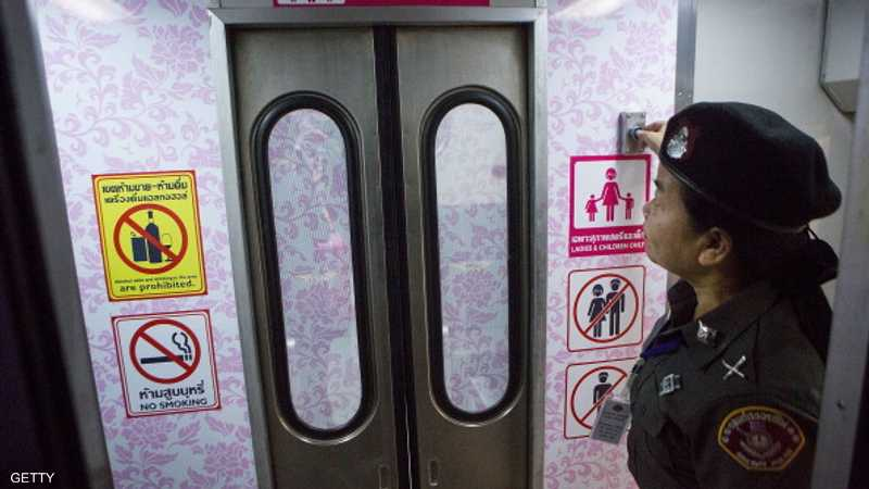 شرطية تفتح الباب لعربة السيدات