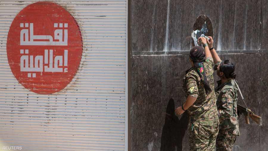 قوات حماية الشعب الكردي أزالت ملصقات داعش من جدران مباني تل أبيض