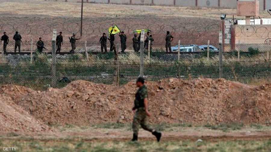 مقاتلون أكراد يلوحون بعلمهم.. وعلى الجانب الآخر جندي تركي يترقب