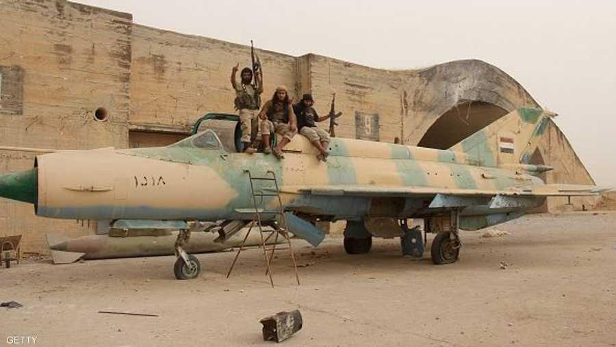 مسلحو المعارضة السورية يعتلون إحدى الطائرات المقاتلة في مطار أبو الظهور
