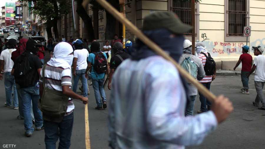 محتج ملثم يرفع عصاه استعداد لمواجهة محتملة مع قوى الأمن