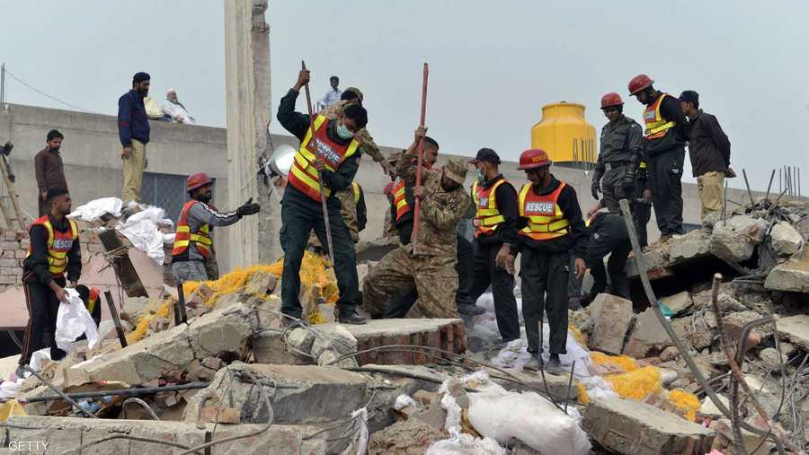 رجال من فرق الإنقاذ في مكان انهيار مبنى المصنع.