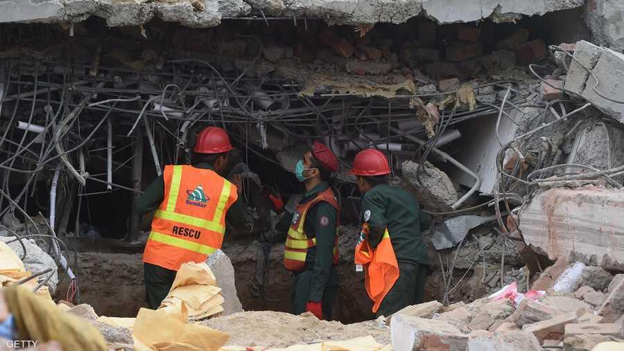 رجال الإنقاذ يبحثون عن خيط حياة بين طبقات المبنى بعد انهياره.