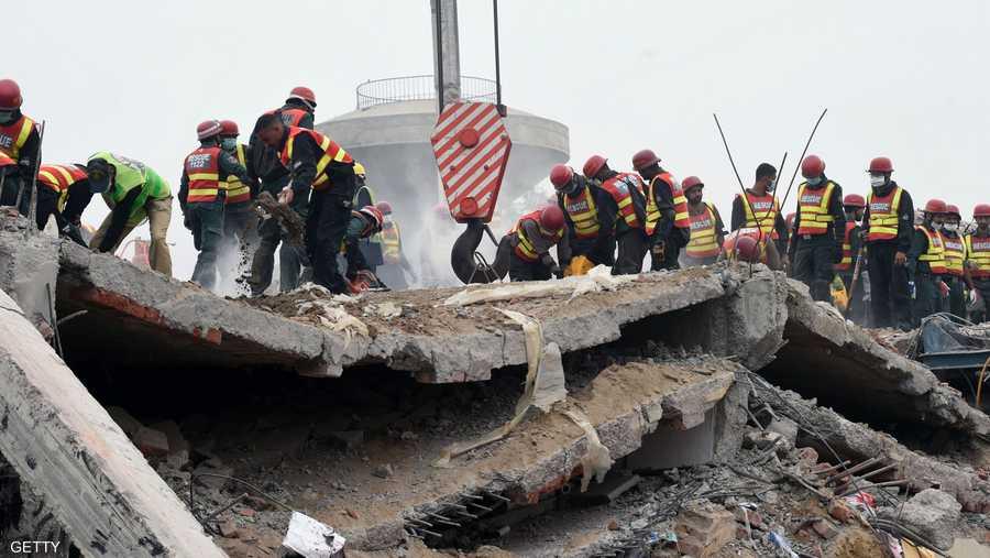 عمال الإنقاذ يحاولون إزالة الركام بآلات بسيطة.