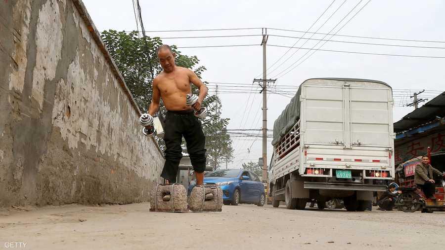 صيني يمشي بحمل اثنين من الحجارة تزن كل منهما 53 كغم