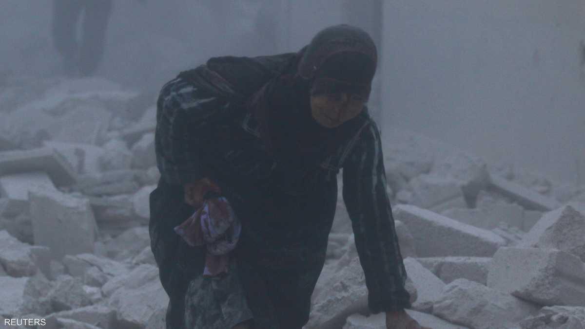 سيدة سورية تخرج من بين أنقاض مبنى دمرته ضربة غارة جوية على حي الأنصاري في شرق حلب الأربعاء 7 ديسمبر 2016.