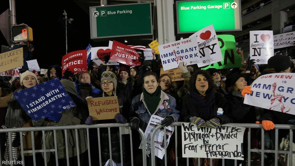 لافتات مناهضة خارج مطار نيويورك لمحتجين على القرار السابق.