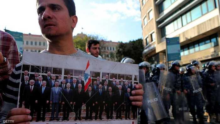 متظاهر يرفع صورة يتهم فيها وزراء لبنانيين بالفساد