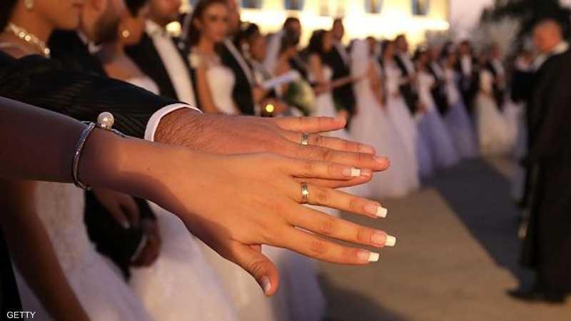 عروس تشهر خاتم الزواج مع يد عريسها