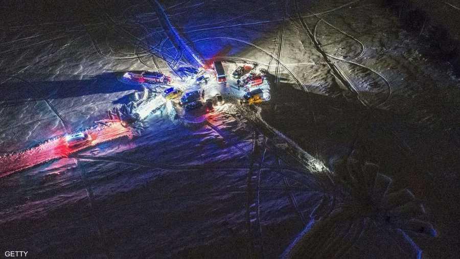 وفرق النجدة بالقرب من الحطام وسط الثلوج