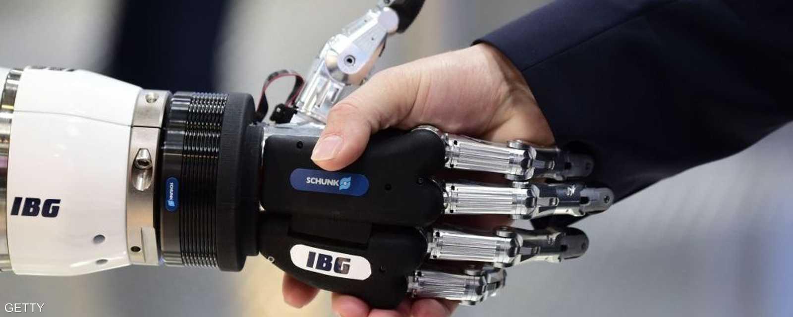 """صورة لشخص يصافح يد روبوت من صنع شركة """"آي بي جي أوتوميشن"""""""