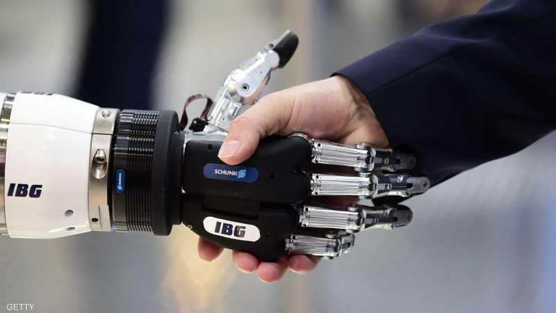 صورة لشخص يصافح يد روبوت من صنع شركة