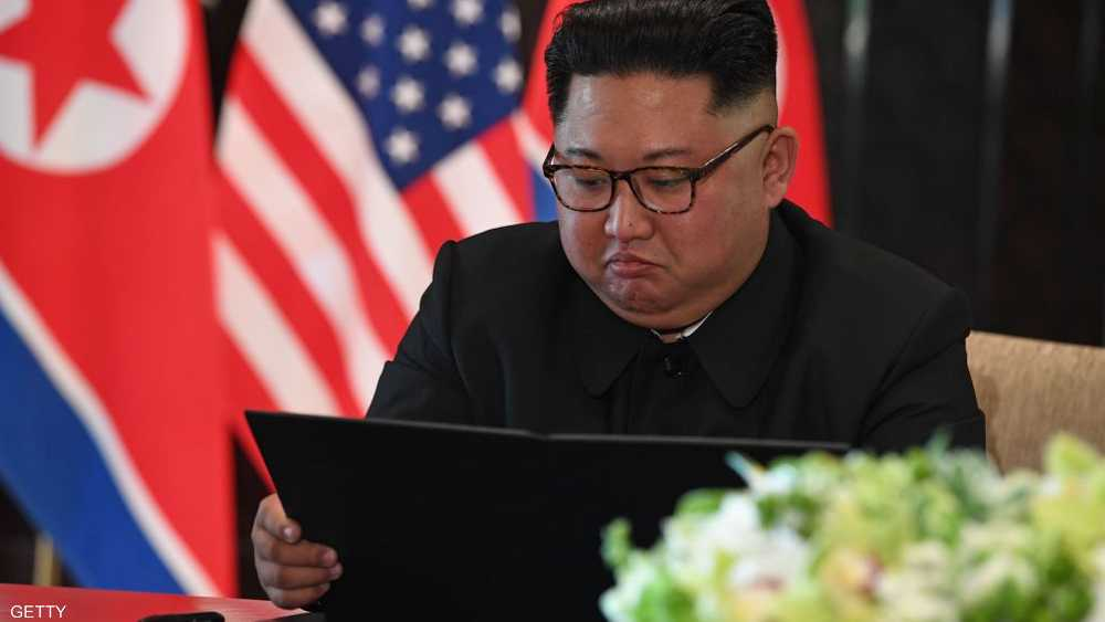 كيم يتأمل الوثيقة الموقعة مع ترامب