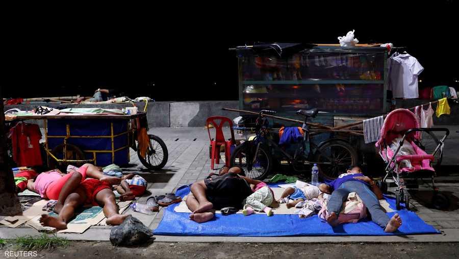 مشردون يفترشون الأرض في حي فقير بمانيلا