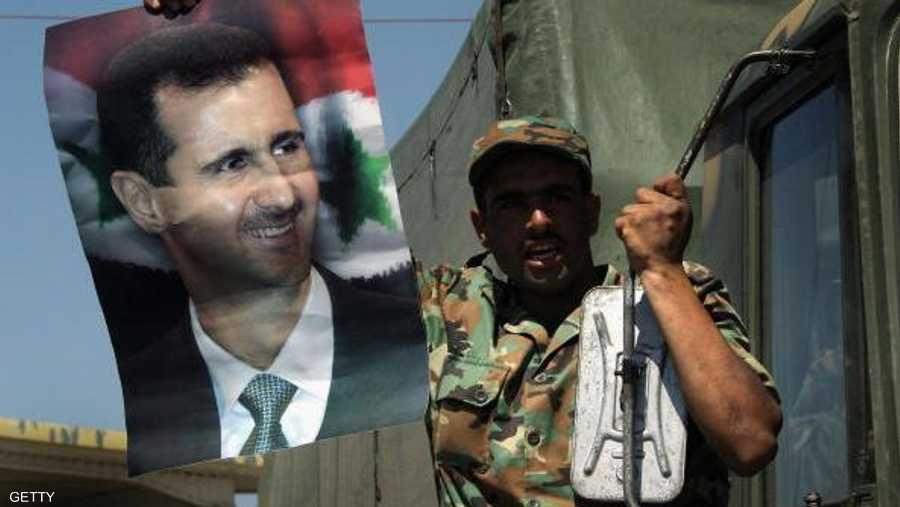 جندي سوري يرفع صورة الأسد.