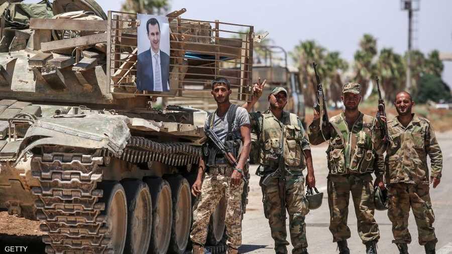 جنود امام دبابة تحمل صورة الأسد.