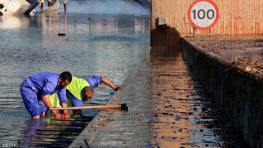 عمال البلدية في الكويت يحاولون تصريف المياه بأحد الشوارع