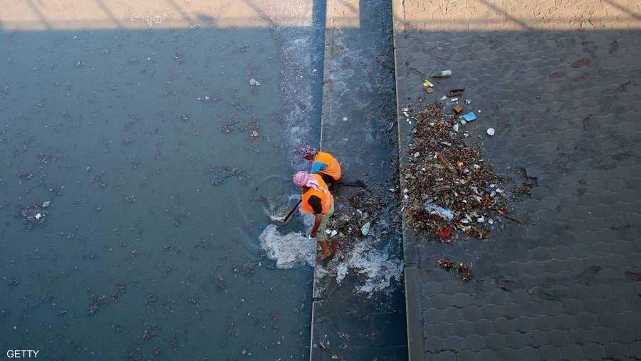 عمال البلدية يحاولون تصريف مياه الأمطار