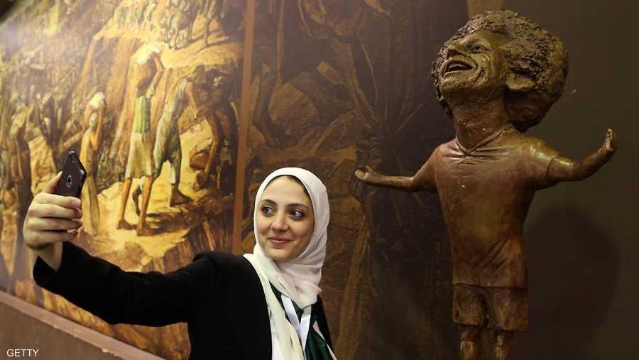 إحدى المشاركات في منتدى شباب العالم مع تمثال صلاح
