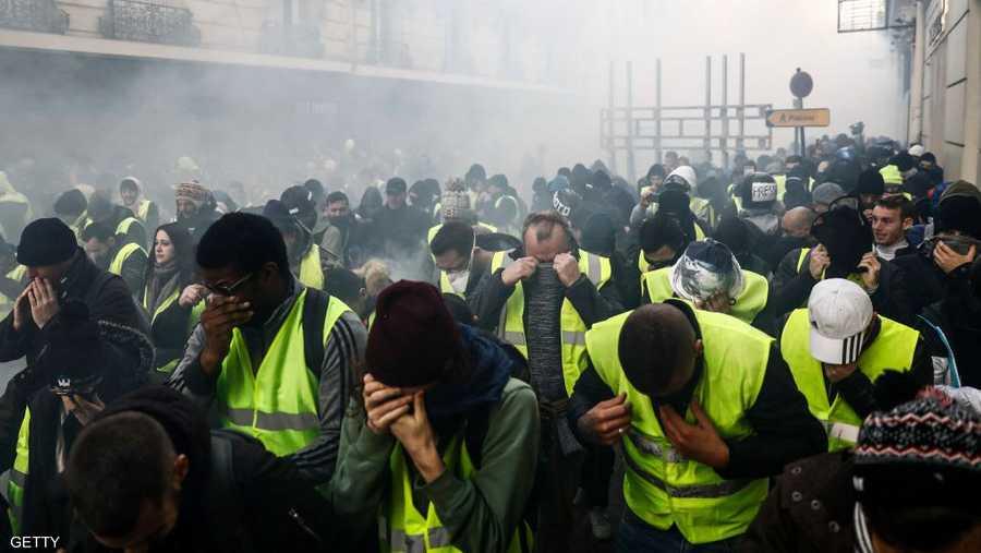 متظاهرون يغطون وجوههم بعد إطلاق الغاز المسيل للدموع عليهم