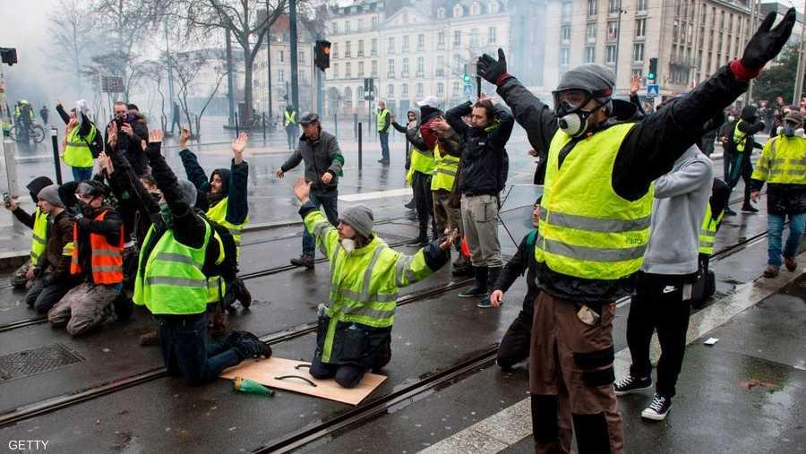 متظاهرون يواجهون الشرطة بأذرع مفتوحة في إشارة إلى سلميتهم