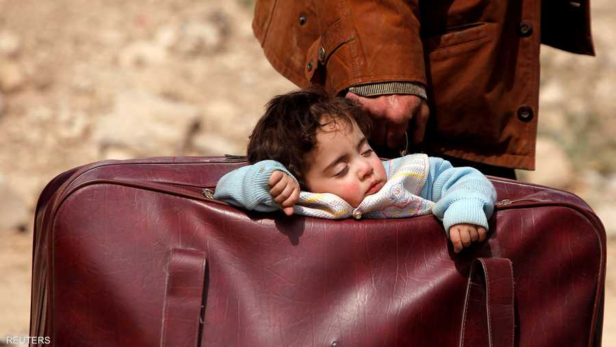 طفلة سورية نائمة في حقيبة