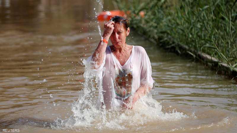 حاجة مسيحية تتبرك بمياه نهر الأردن في موقع المغطس