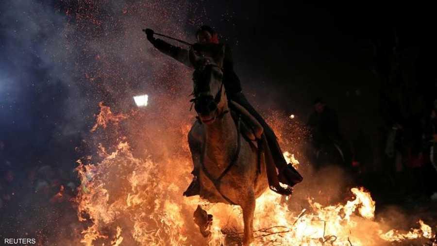 """شهدت قرية """"سان بارتولومي دي بيناريس""""، شمالي غرب مدريد الإسبانية، انطلاق مهرجان """"لومينارياس""""، الذي يركض فيه الحصان تلو الآخر وعليه فارسه، فوق مواقد النار."""