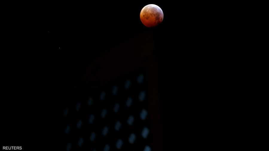 الصبغة الحمراء للقمر الدموي هي نتيجة سريان أشعة الشمس عبر الغلاف الجوي الذي يخيم عليه الغبار والتلوث. وتتبعثر الأشعة الزرقاء ذات الطول الموجي الأقصر والأكثر قابلية للانكسار خارج ظل الأرض.