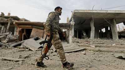 مقاتل قوات سوريا الديمقراطية أمام مقر سابق داعش بمدينة هجين