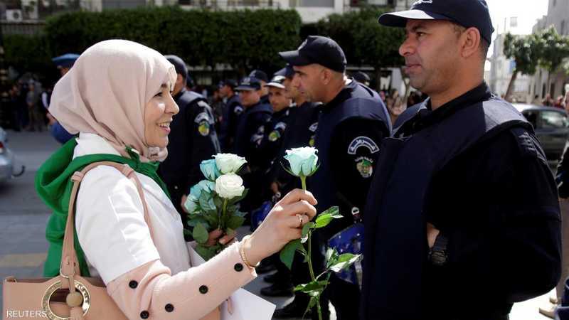 إحدى المتظاهرات تقدم زهورا إلى ضابط شرطة
