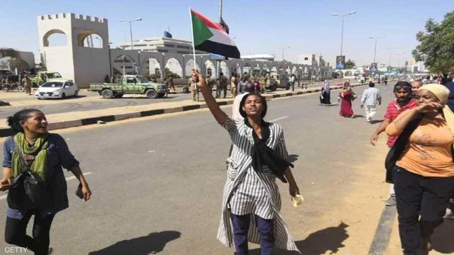 فتاة ترفع علم السودان خلال التظاهرات الاحتجاجية
