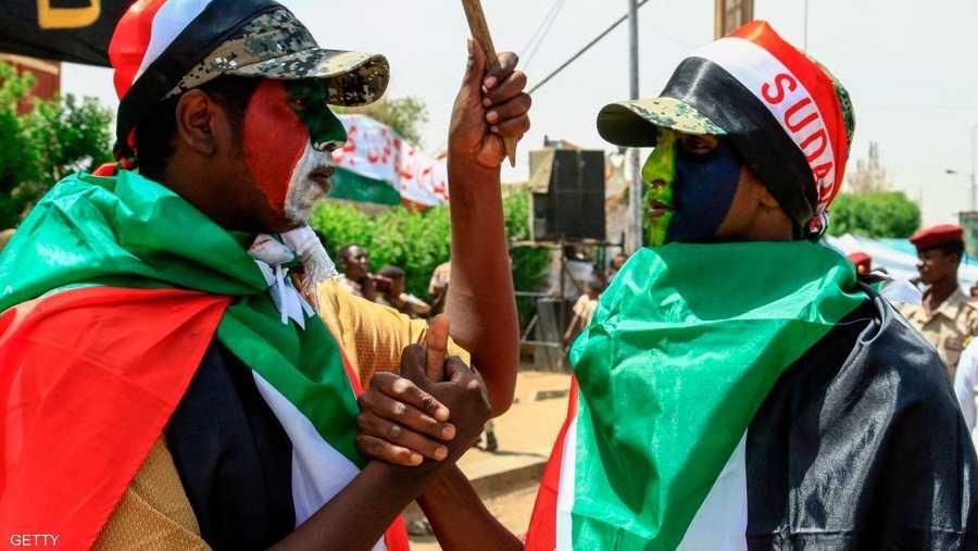 محتجان يرسمان على وجههما علم السودان الجديد والقديم