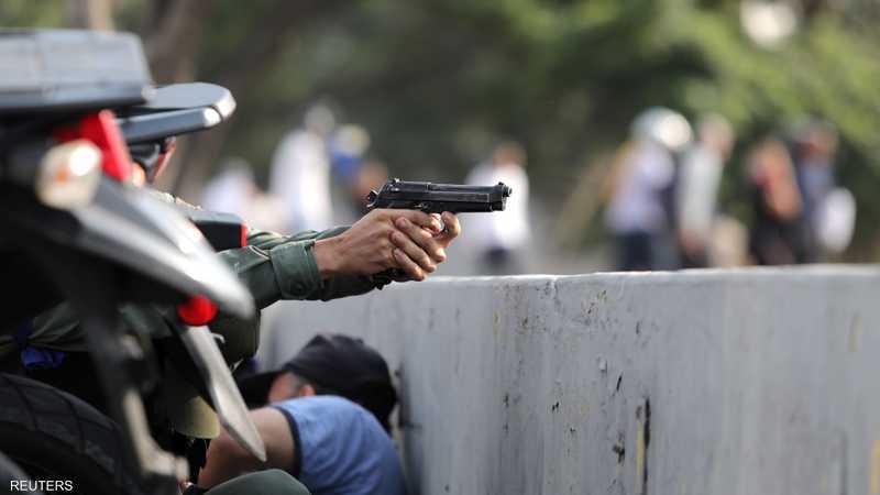 عسكري فنزويلي يشهر سلاحه خلال اشتباكات مع قوات الأمن قرب قاعدة جوية في كاراكاس