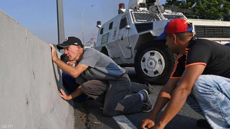 واحتمى عسكريون ومدنيون معارضون بجدار اسمنتي في كاراكاس، بعدما تحولت التظاهرات قرب القاعدة العسكرية إلى اشتباكات مسلحة.