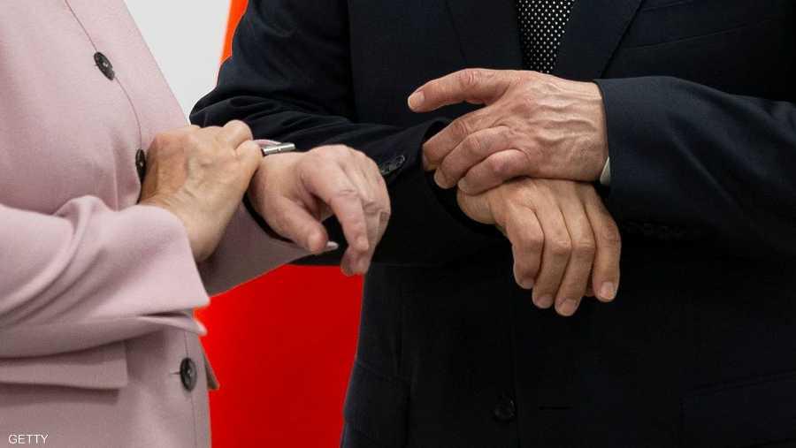 بوتن وميركل ينظران إلى ساعتي اليد في وقت واحد