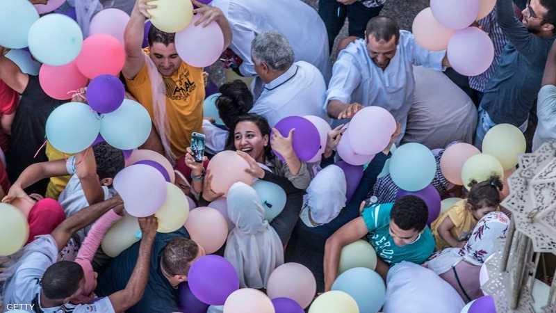 مصر.. يحاولون فرحين الإمساك ببالونات العيد