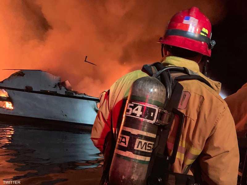 رجال الإطفاء يحاولون احتواء الحريق في السفينة