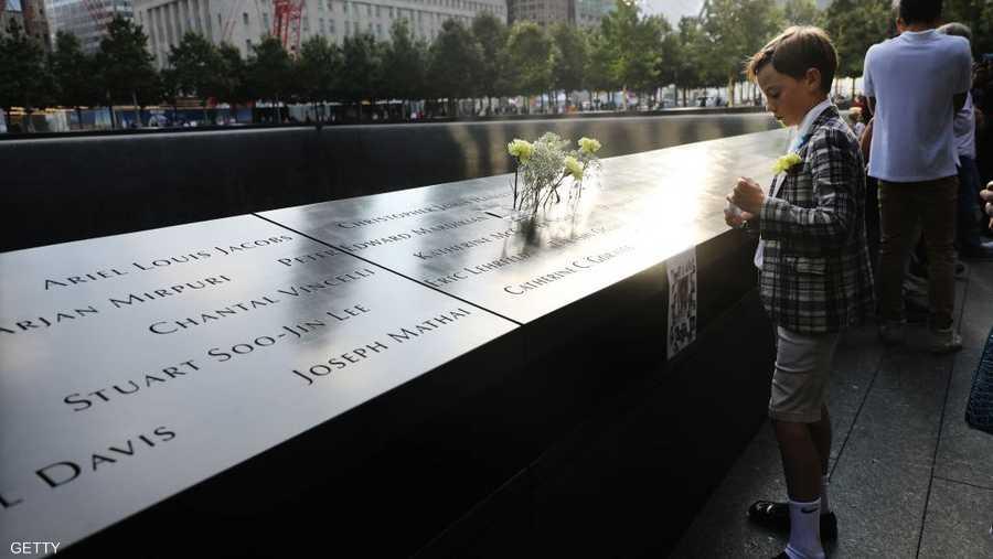 الطفل توم جونسون يقف عند اسم عمه في لوحة الضحايا.