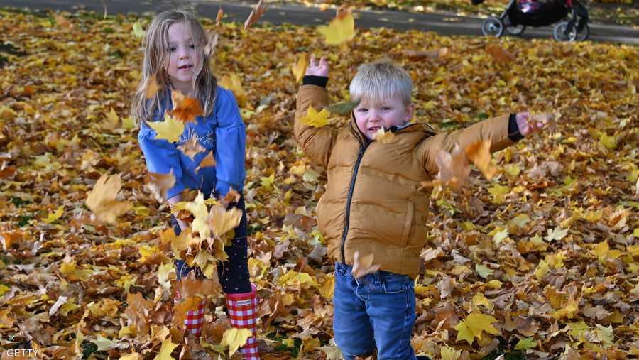 ديفيس موريسون (سنتان) وشقيقته إيسلا روز (5 سنوات) من غلاسكو في اسكتلندا يستمتعان بأوراق الخريف بجانب إحدى البحيرات.