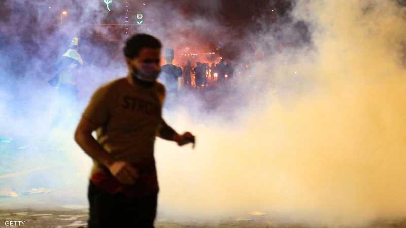 متظاهر عراقي يهرب من قنابل الغاز