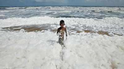 """صور مفزعة.. """"الرغوة السامة"""" تغزو الشاطئ والأطفال لا يأبهون"""