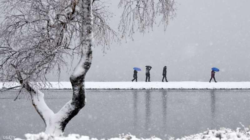 بعض السكان في ألمانيا يسيرون على ضفاف بحيرة وسط الثلوج التي كست كل شيء باللون الأبيض.