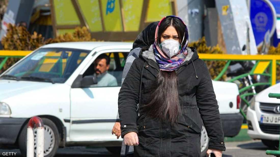 فتاة إيرانية ترتدي كمامة في أحد شوارع طهران
