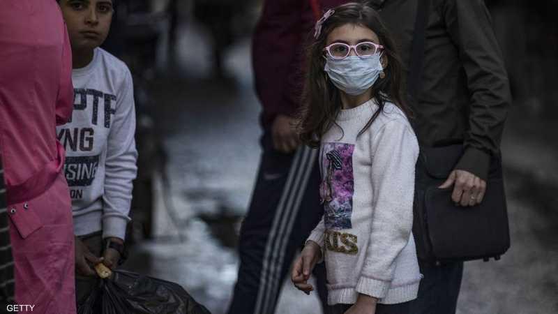 طفلة سورية ترتدي كمامة واقية