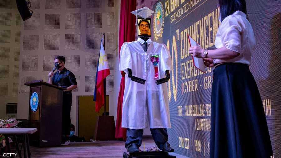 يتقدم الروبوت إلى المنصة كما هي الحال في حفلات التخرج الاعتيادية.
