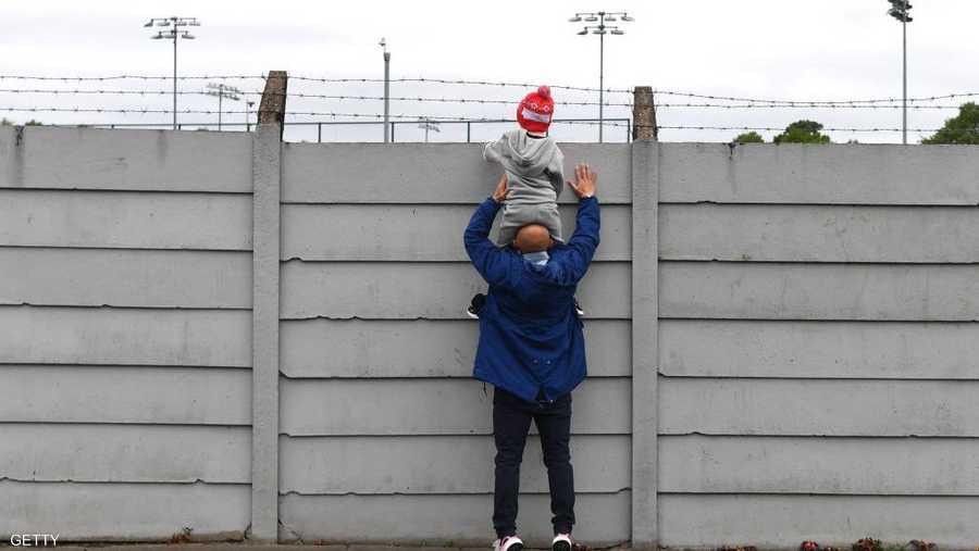 أب يحمل ابنه لمشاهدة تدريبات فريقه المفضل ليفربول.
