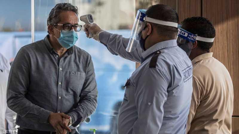 فحص درجة حرارة مواطن مصري للتأكد من سلامته من كورونا