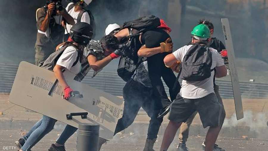 متظاهرون يحملون جريحا جراء الاشتباكات مع الشرطة