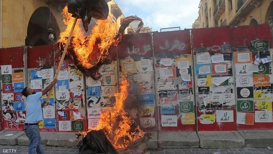 متظاهر يقذف بلافتة مشتعلة خلف الجدار الأمني